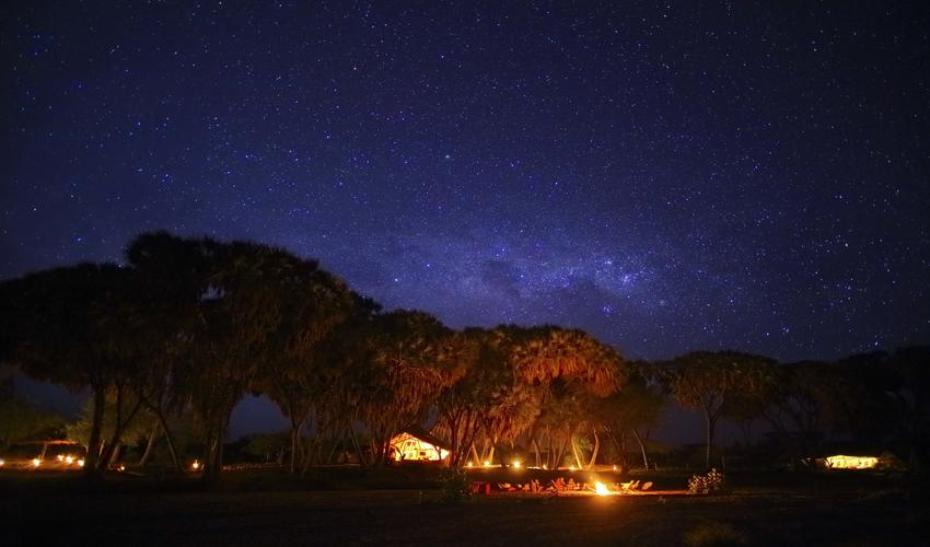 Enjoy a torch-lit dinner in the dry river bed under the immense African skies