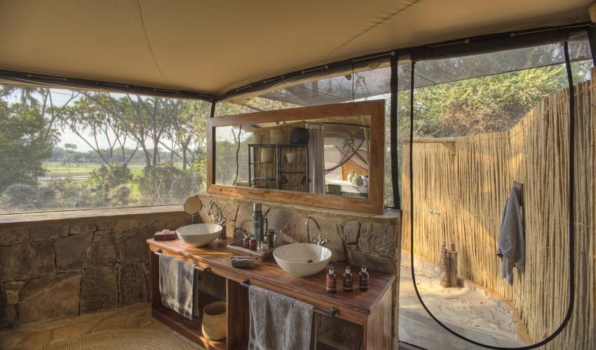 Roho ya Selous - guest tent bathroom leading to outdoor shower