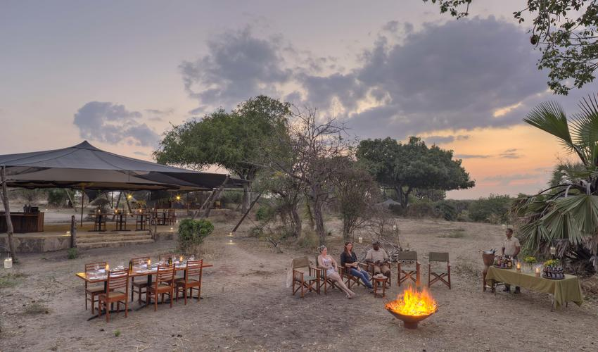 Roho ya Selous - guests enjoying sundowners by the campfire
