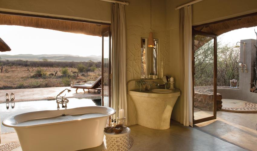 Bathrooms boast indoor and outdoor showers and a bath with amazing views of the endless Bushveld