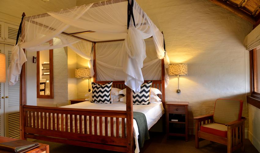 The Victoria Falls Safari Lodge's king suites have an open plan lounge area with a guest toilet/ cloakroom downstairs as well as a private balcony. An open staircase leads up to the bedroom and en suite raised bathroom with a luxury bath and separate shower.
