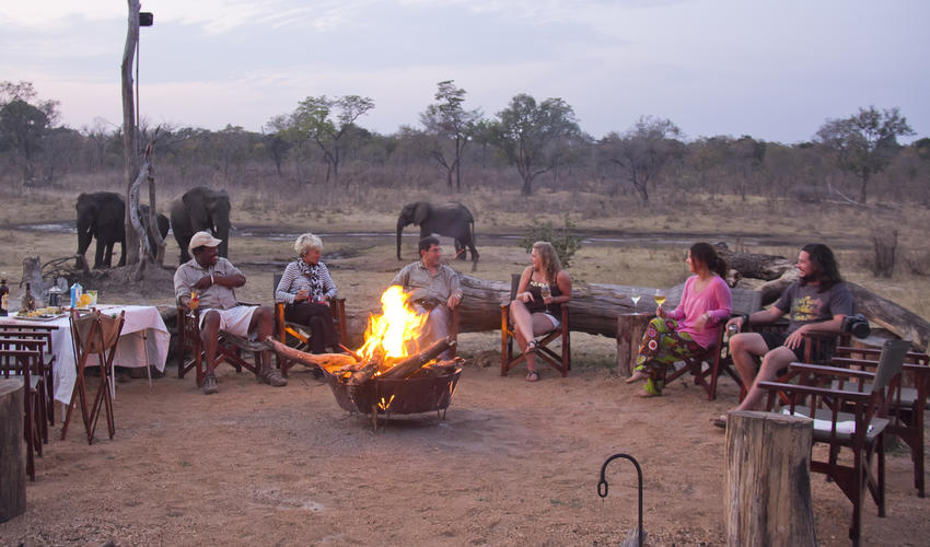 Sundowners around the camp fire with the ele's at the waterhole