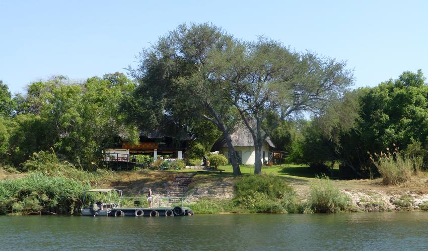 The central lodge with dining room and sun/dining deck over looking the river and viewing lounge above. Two story Owl House is in the centre of the picture. The pontoon at the foot of the steps is for guest use for sitting and relaxing, or fishing, and is where boats depart for cruises, fishing and visits to the local village. The river rises and falls by about 5 metres seasonally. The trees and foliage are perfect for a wide range of birdlife and guests can watch game on the opposite banks in the Zambezi National Park.