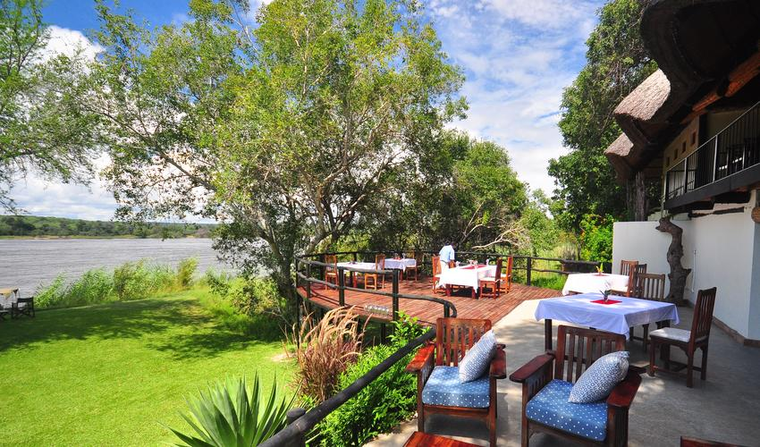 In 2014 we built a deck off the front verandah to make sure all guests could eat alfresco if they wish, and also enjoy the shade of the overhanging waterberry trees. At night we use subtle solar lights and guests can watch the hippos that frequently graze the lawns by the river. When the river is high the water runs under the deck. In the heat of the day guests can retreat to the upstairs lounge with amazing views over the Zambezi National Park across the river.