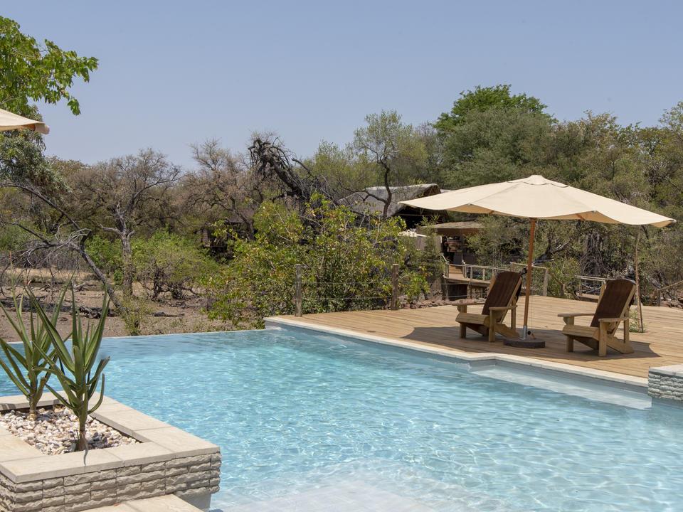 Der Pool mit Blick auf das Wasserloch vor dem Camp