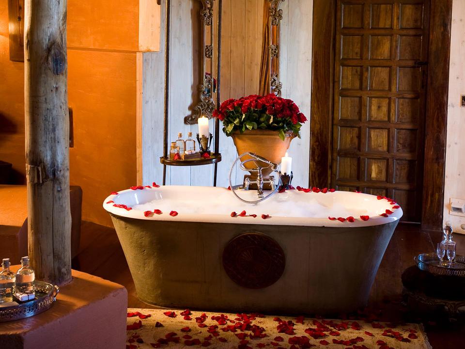 Mit einem Herzstück aus roten Rosen hat zwei Handwaschbecken, Dusche, Badewanne mit Kronleuchter und separatem WC