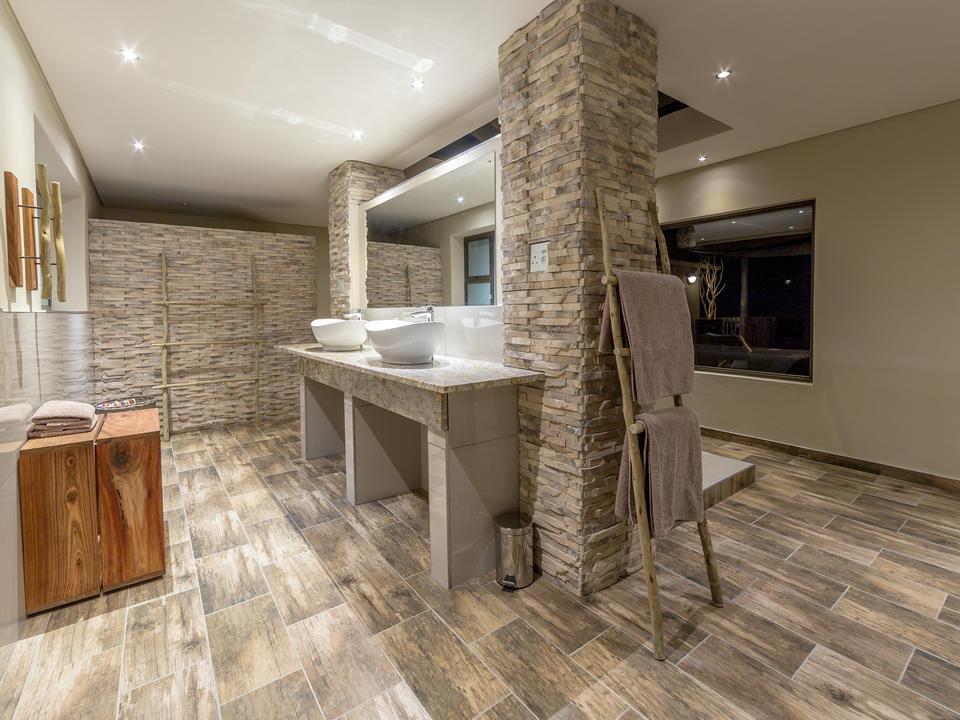 Elegantes Badezimmer der Junior Suite mit ebenerdiger Dusche, separatem WC, Doppelwaschbecken und freistehender Badewanne