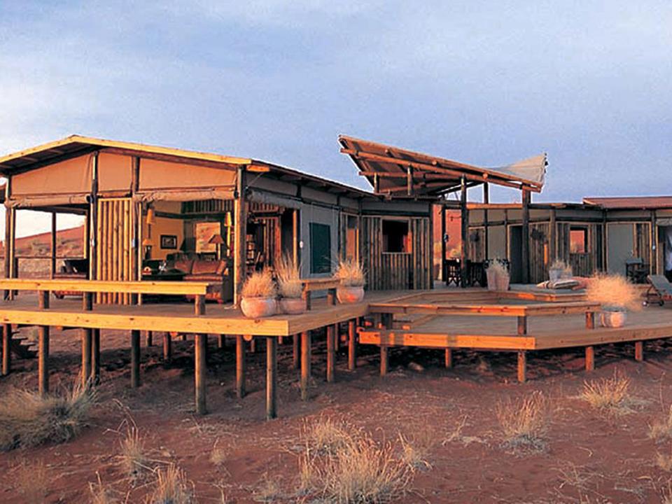 Eine Kombination aus Holzkonstruktionen und Leinwandjalousien, die sich bis zur Wüste hinüber öffnen