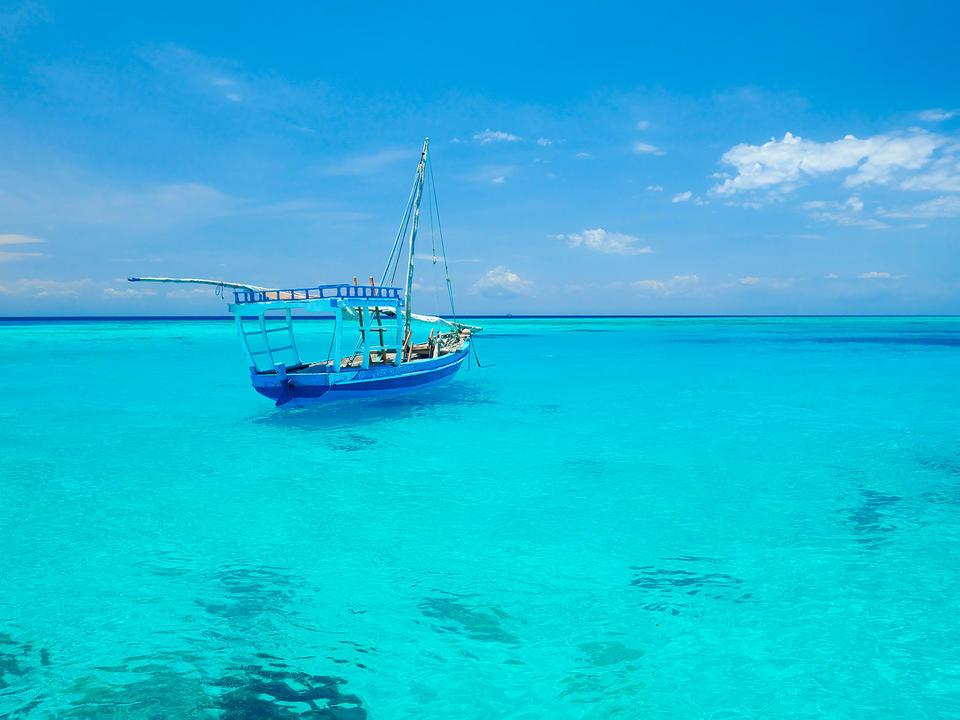 Ein Dhow umgeben von türkisfarbenem Wasser