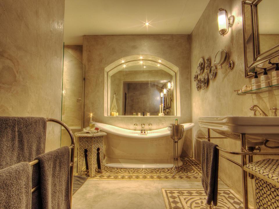 Innenansicht des Standardzimmers und der Anzugbäder der Chobe Game Lodge mit Doppelwaschbecken, Badewanne und separater Dusche